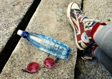 vandflaske-og-solbriller-ligger-paa-fliser